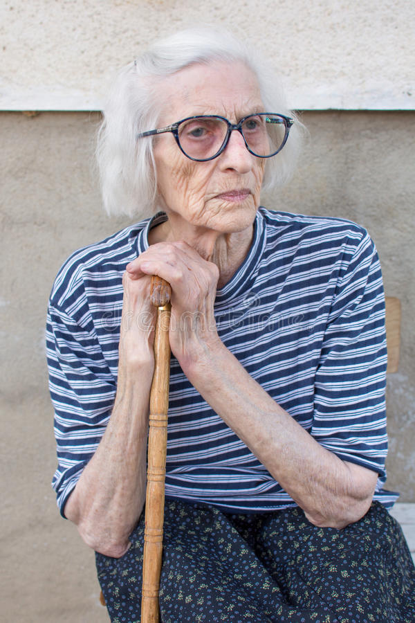 Senior women supporting on a walking cane. Senior woman supporting on a walking cane outdoors royalty free stock images