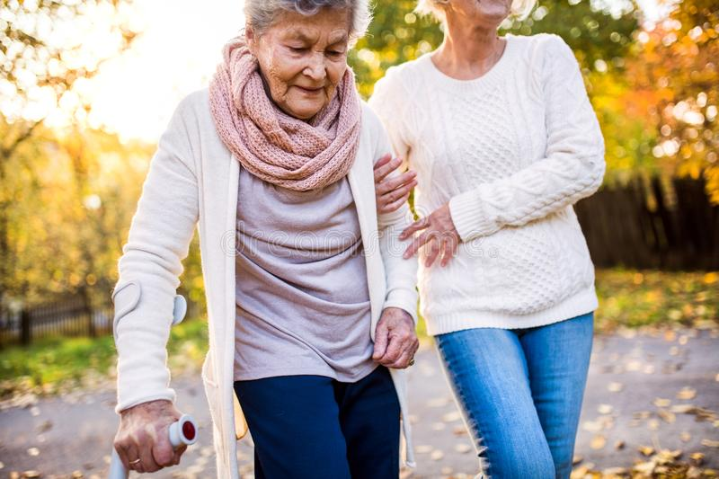 Senior women on a walk in autumn nature. An elderly women with crutch and her unrecognizable senior daughter walking outside stock images