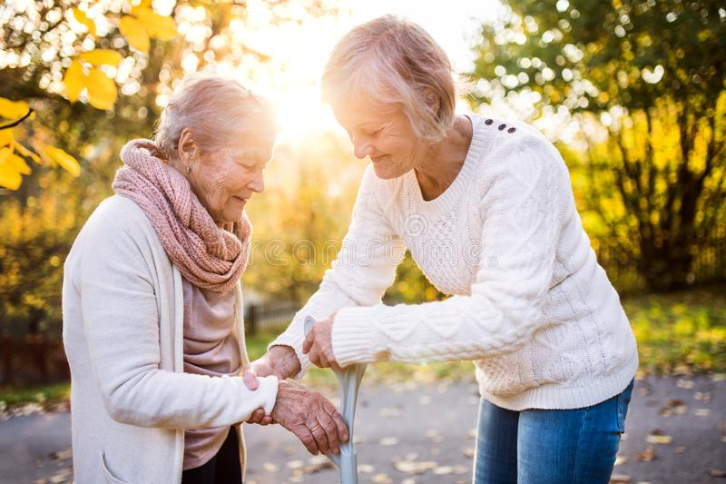 Senior women on a walk in autumn nature. An elderly women with crutch and her senior daughter walking outside stock photo