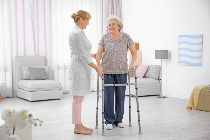 Senior woman with walking frame and caregiver. Senior women with walking frame and caregiver at home stock photos