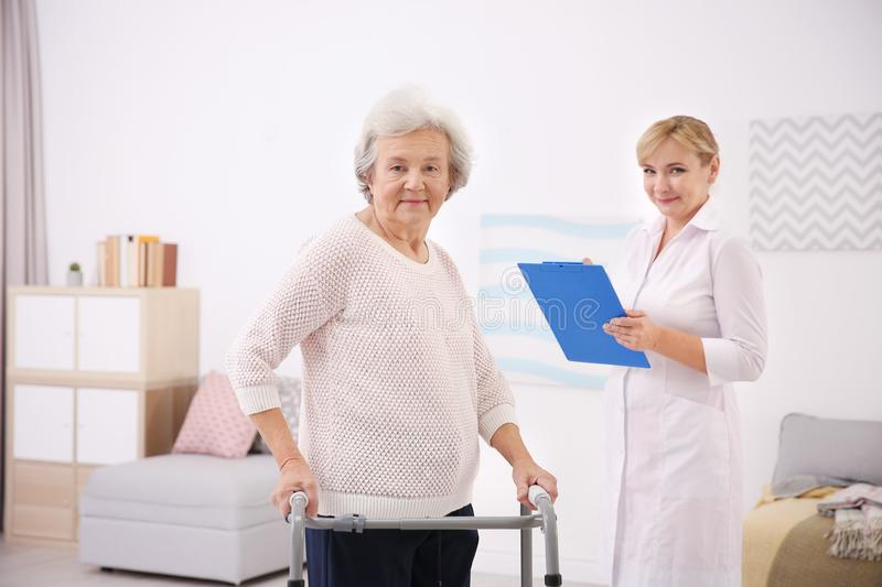 Senior woman with walking frame and caregiver. Senior women with walking frame and caregiver at home royalty free stock photos