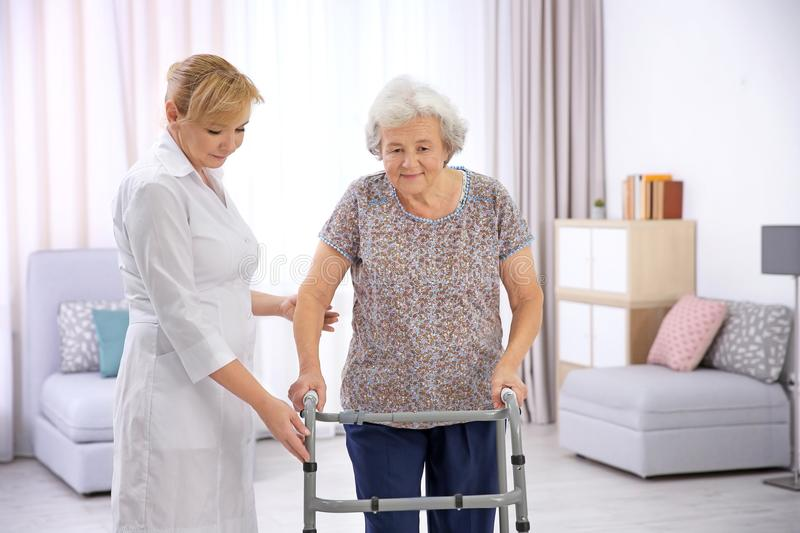 Senior woman with walking frame and caregiver. Senior women with walking frame and caregiver at home stock photo
