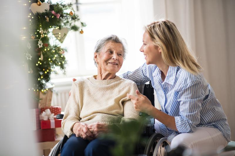 A senior woman in wheelchair with a health visitor at home at Christmas time. royalty free stock photos