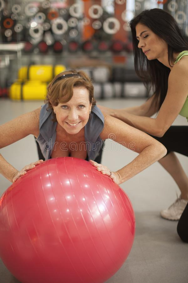 Senior woman working out with personal trainer royalty free stock photos