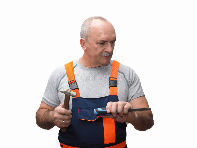 The senior worker with the chisel. The senior worker in jumpsuit holding hammer stock photography