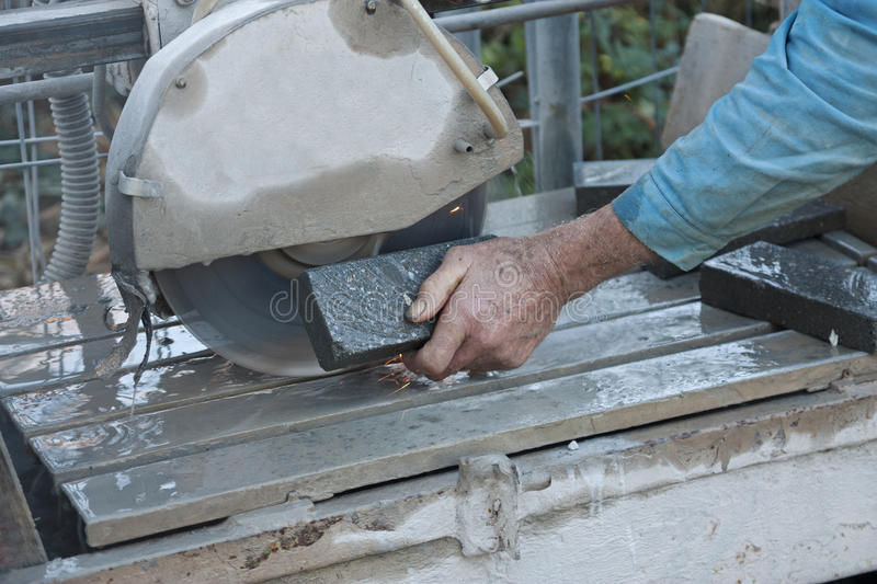 Senior worker cutting tile with a stone saw stock photos