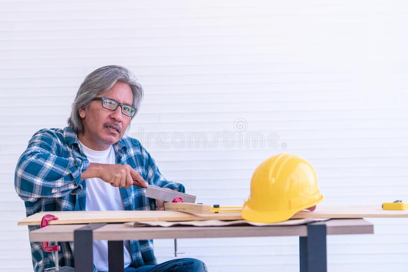 Senior worker saw on wood workshop table for home improvement project. Senior worker is saw on wood workshop table for home improvement project royalty free stock image