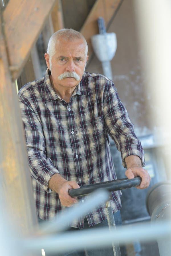 Senior worker turns valve stock images