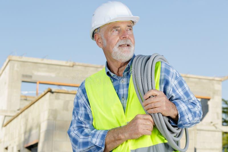 Senior worker unfolding rubber hose stock image