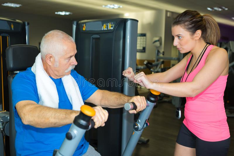 Senior working out with personal trainer standing beside him stock images