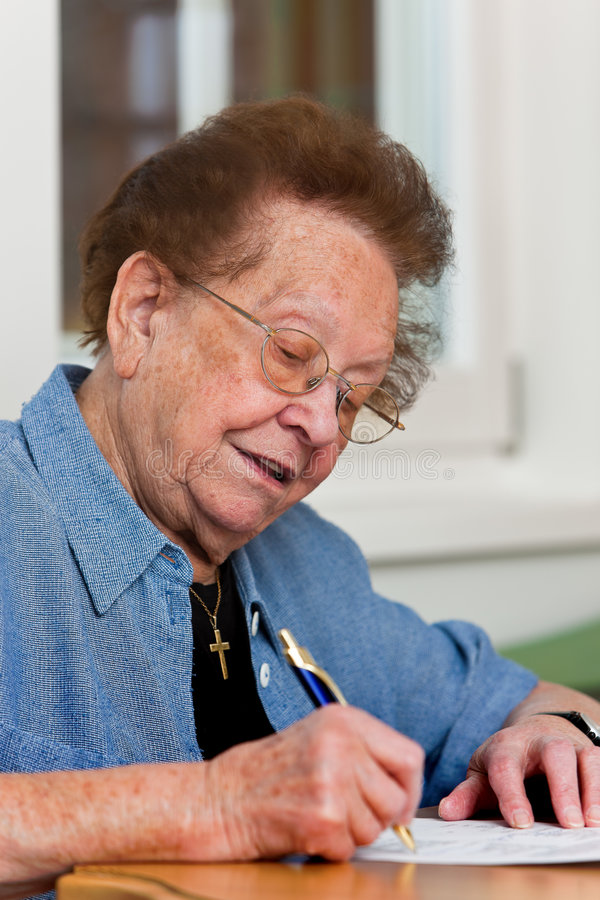 Senior writes a letter. Old woman writes a letter royalty free stock photo