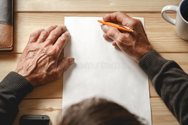Senior writes a testament. The old man wrote a testament, sitting at a wooden table stock photos