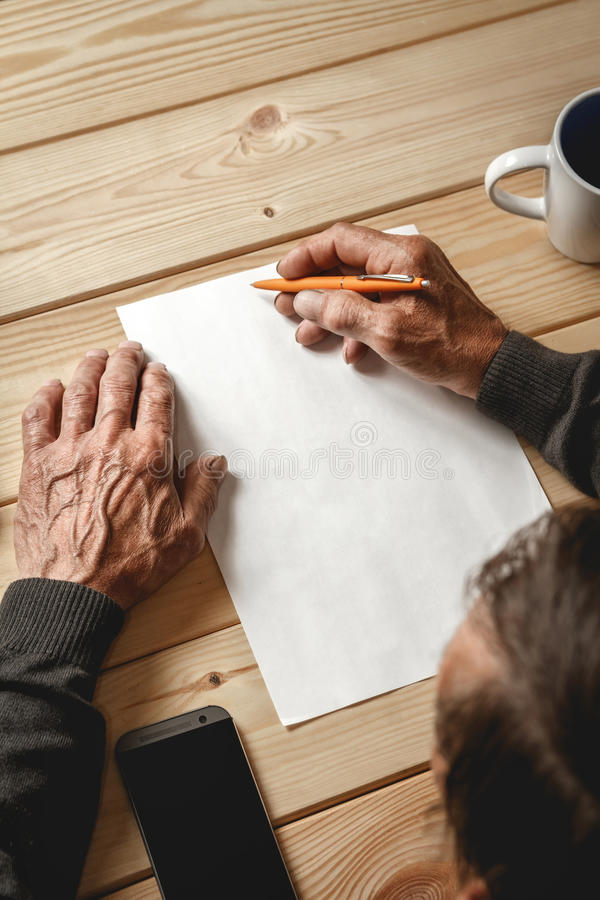 Senior writes a testament. The old man wrote a testament, sitting at a wooden table stock image