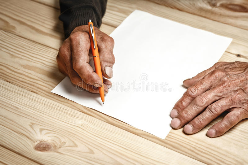 Senior writes a testament. The old man wrote a testament, sitting at a wooden table royalty free stock images