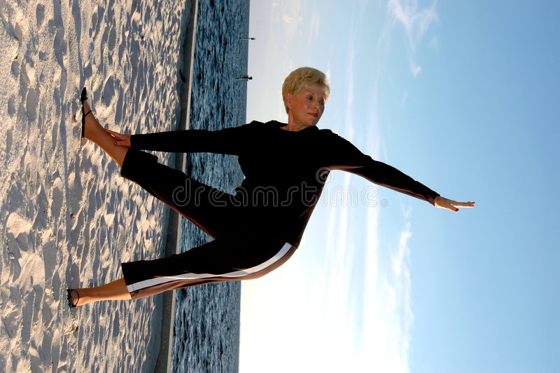 Senior yoga pose. A senior woman doing yoga triangle pose on the beach royalty free stock images