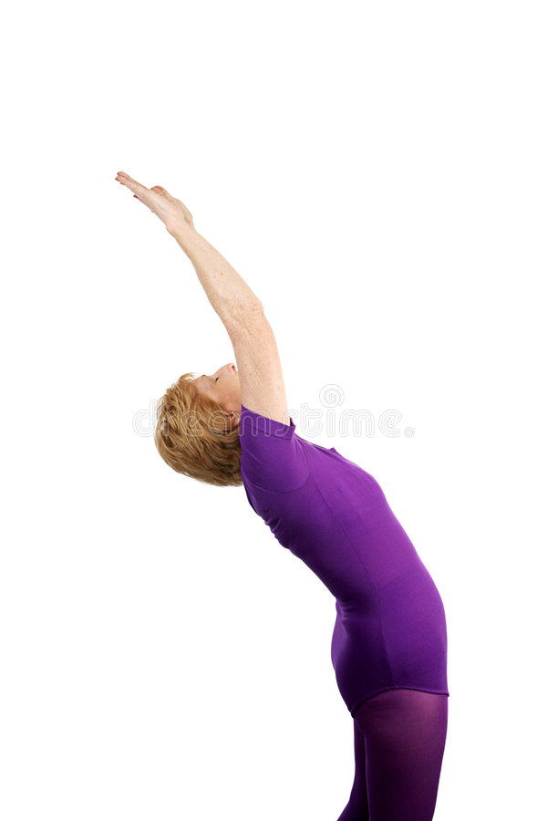 Senior Yoga - Salute to Sun. A seventy year old senior lady performing the yoga pose Salute to the Sun. Isolated on white royalty free stock images