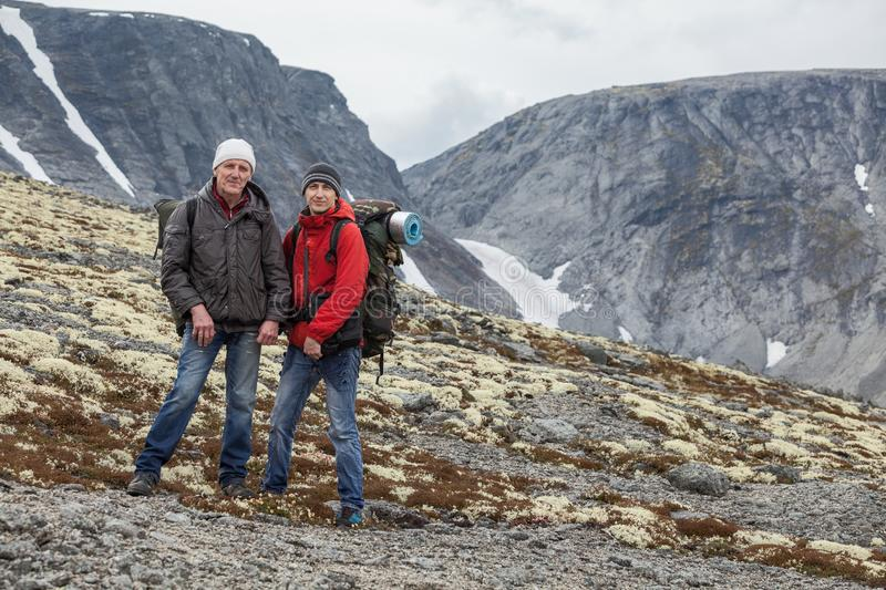 Senior and young backpakers standing in mountains, hiking together, copyspace stock photos