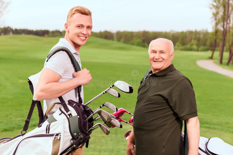 Senior and young golf players with equipment. Lets go. Senior and young golf players standing on green course with special equipment royalty free stock image