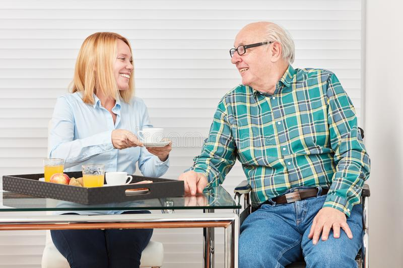 Senior and young woman having breakfast at home stock photos