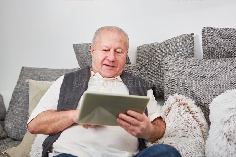 Senior z pastylka komputerem obrazy stock