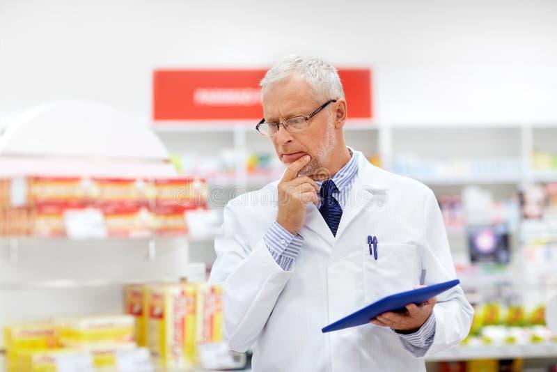 Senior z pastylka komputerem osobistym przy apteką obraz stock