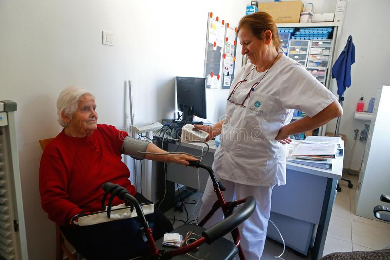 Senior z pielęgniarką na dziennej ciśnienie krwi kontroli karmiący dom w Mallorca szerokim obrazy stock