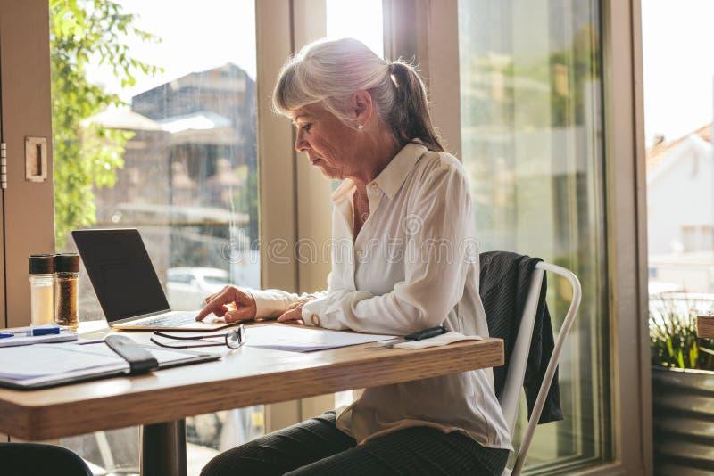 Senior zakenvrouw werkt aan laptop in de koffiewinkel stock foto