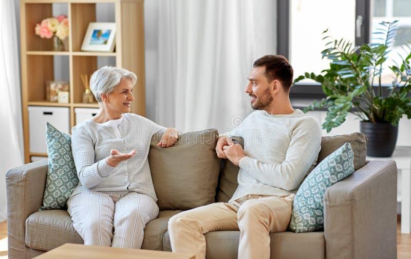 Seniora macierzysty opowiadać dorosły syn w domu fotografia stock
