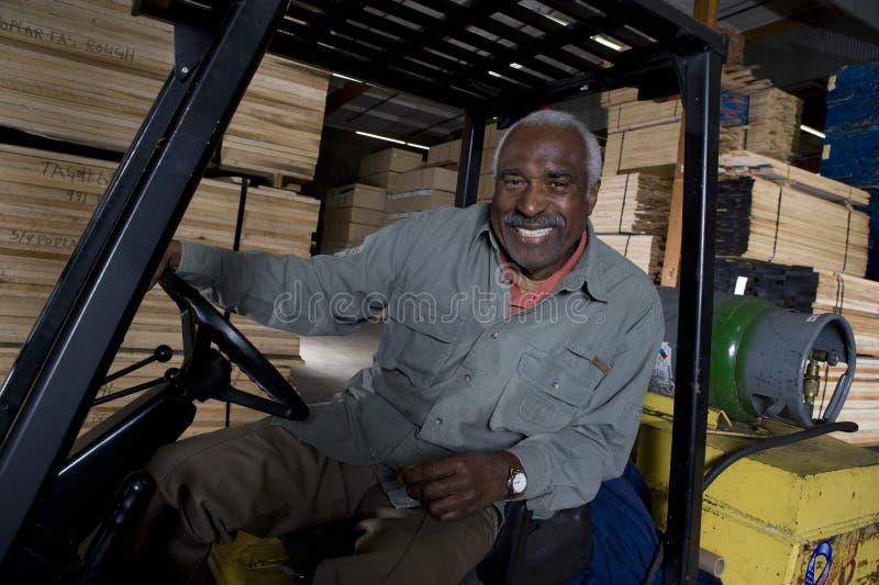 Seniora pracownika Magazynowy obsiadanie W Forklift fotografia stock