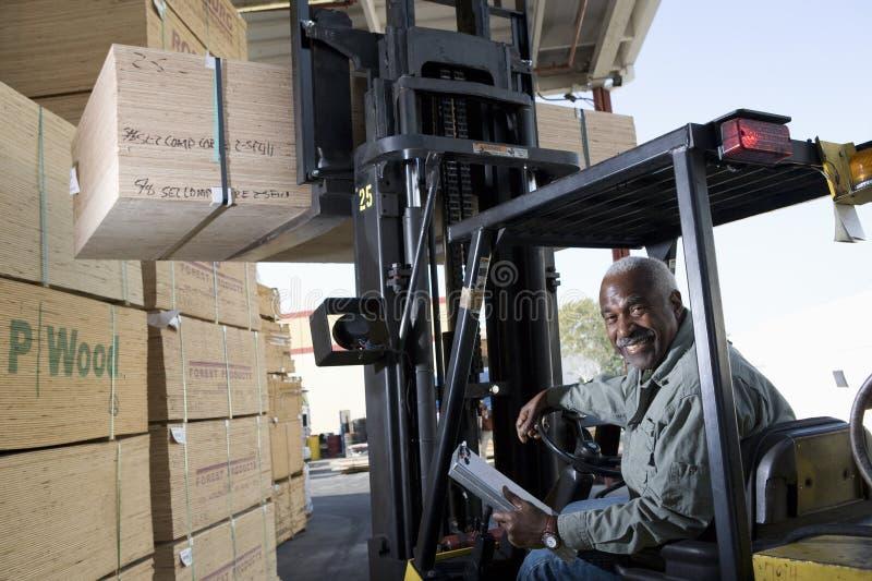 Seniora pracownika sztaplowania Magazynowy drewno Forklift zdjęcia royalty free