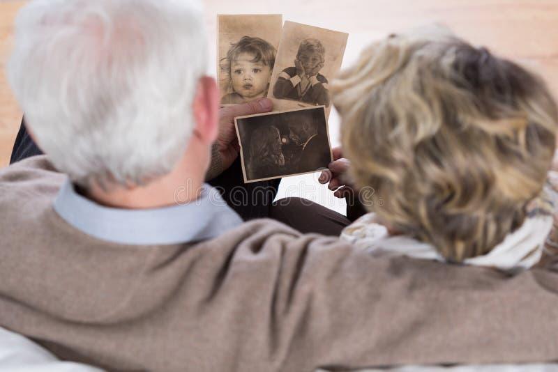 Senioren, die alte Bilder betrachten stockbilder