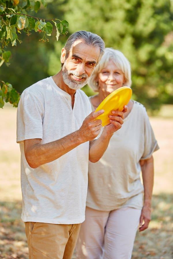 Senioren, die mit einem Frisbee spielen lizenzfreie stockfotografie