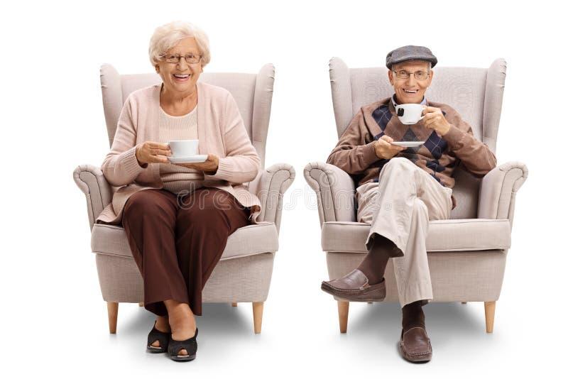 Senioren gesetzt in den Lehnsesseln, die Tee trinken lizenzfreie stockfotografie