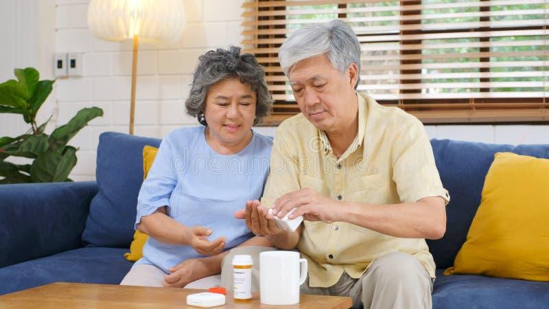 Seniorenpaar nehmen Medikamente für ältere gesunde Lebensweise, während sitzen auf Sofa im Wohnzimmer, Rentner lizenzfreies stockfoto