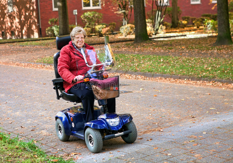 Seniorin with electric scooter royalty free stock photography