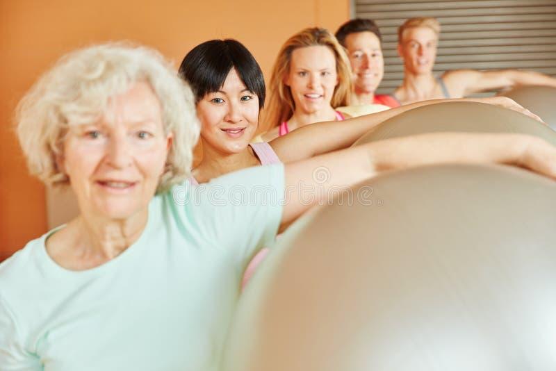 Seniorin på konditiongrupp med bollen royaltyfri foto