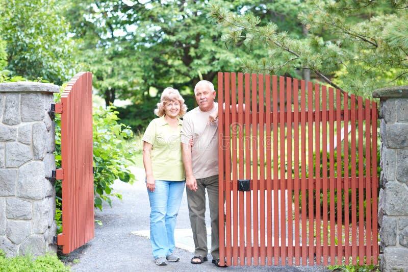 Seniors. Smiling happy elderly seniors couple near the home stock image
