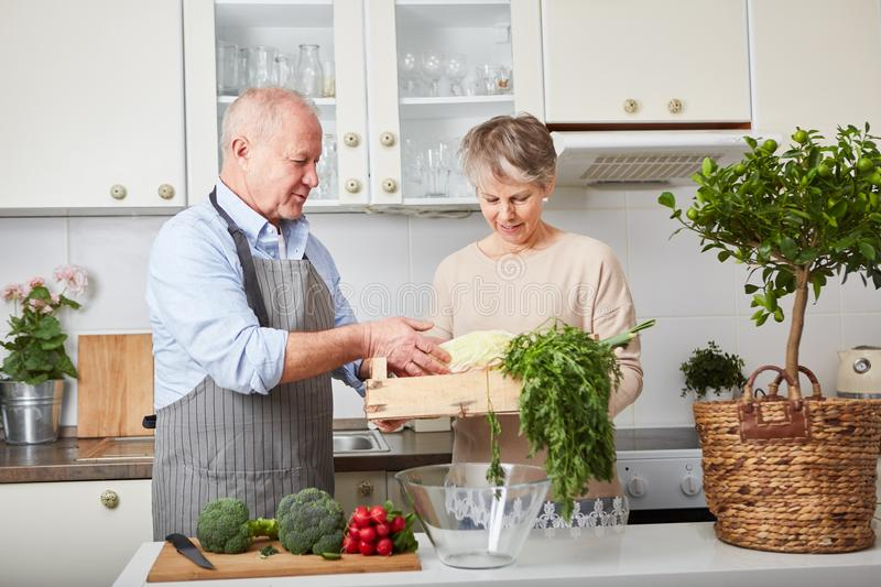 Seniors as couple cooking together. In kitchen with vegetables stock image