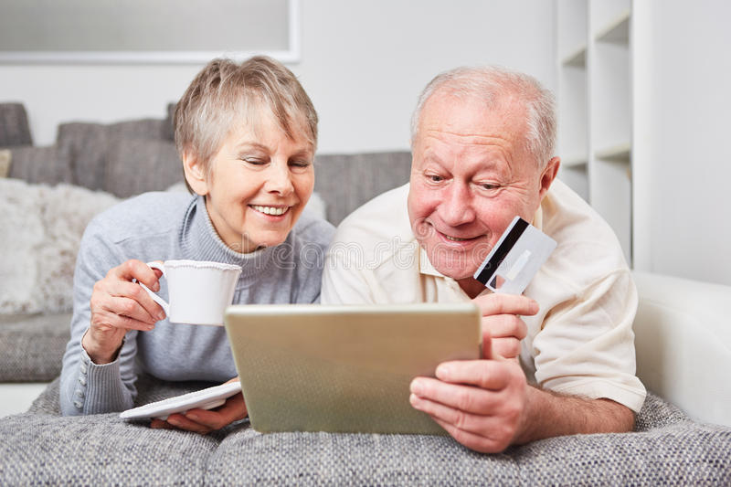 Seniors as couple on the couch. Listen to music online royalty free stock image