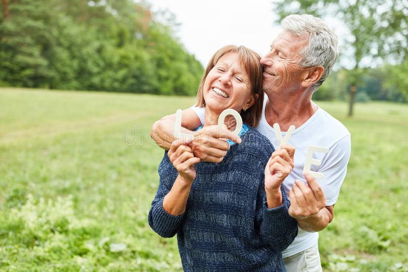 Seniors as a happy loving couple in the park royalty free stock photo