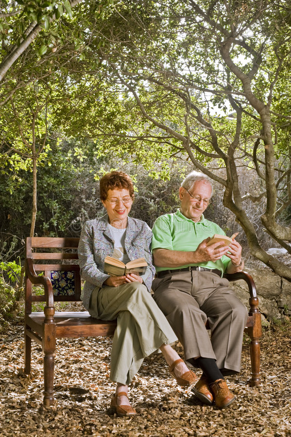 Seniors on a bench. Seniors couple sitting on a bench with a cat in the park stock photo