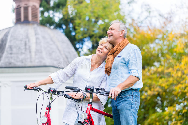 Seniors with bike in front of chapel or church. Seniors, couple of men and woman, with bike in front of chapel or church stock photography