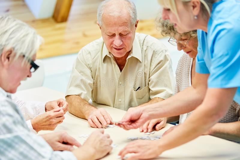 Seniors and a caregiver while playing. Group of seniors with dementia and caregiver playing with puzzle in retirement home stock photos