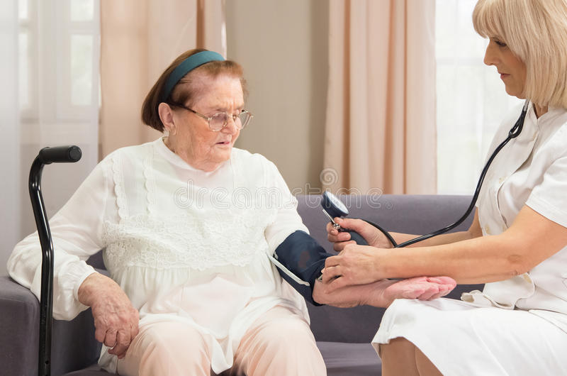 Seniors. Caregiving nurse is doing a blood pressure test to a senior female stock photo