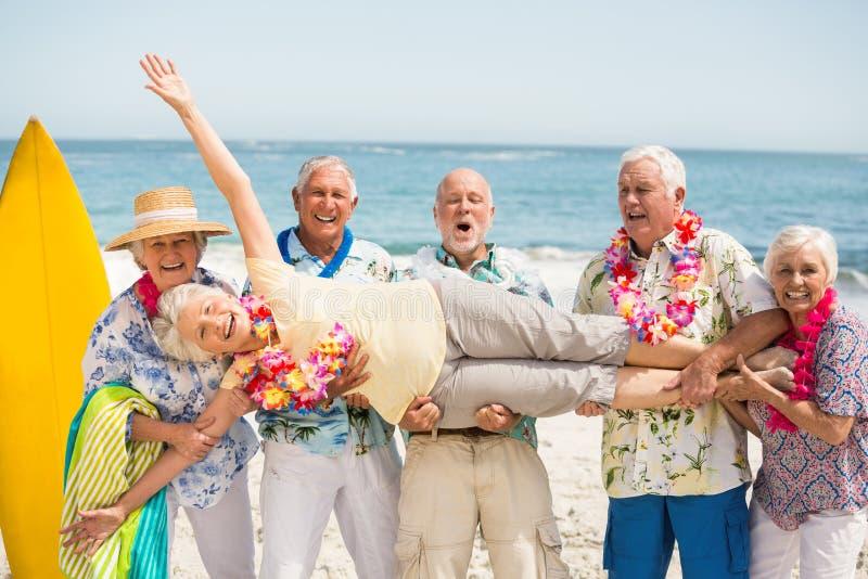Seniors carrying senior woman. Seniors carrying senior women on a sunny day royalty free stock photography