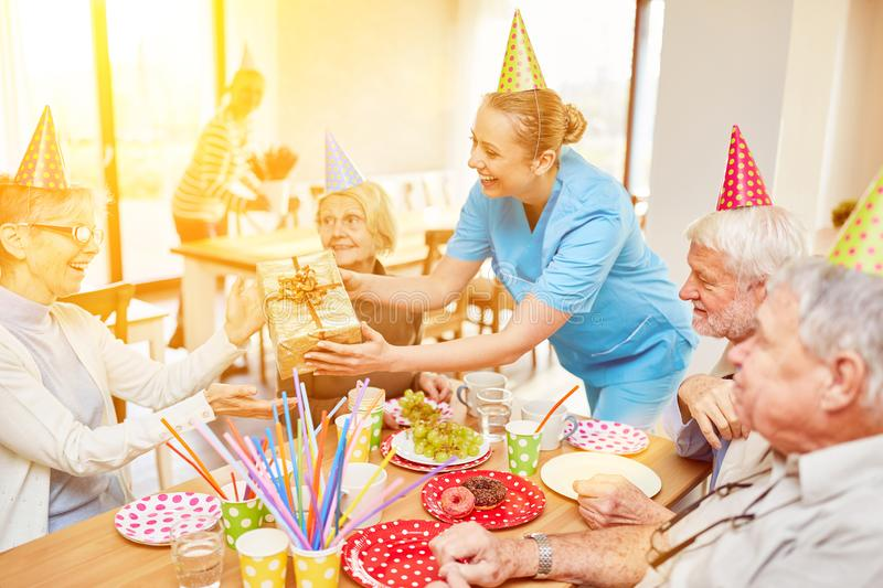 Seniors celebrate birthday in nursing home. Seniors celebrate birthday together in the retirement home with cake and gift royalty free stock images