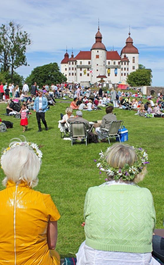 Seniors celebrating midsummer. Old women with flower in their hair celebrating midsummer at Lacko castle close to lake Vanern, Sweden royalty free stock image