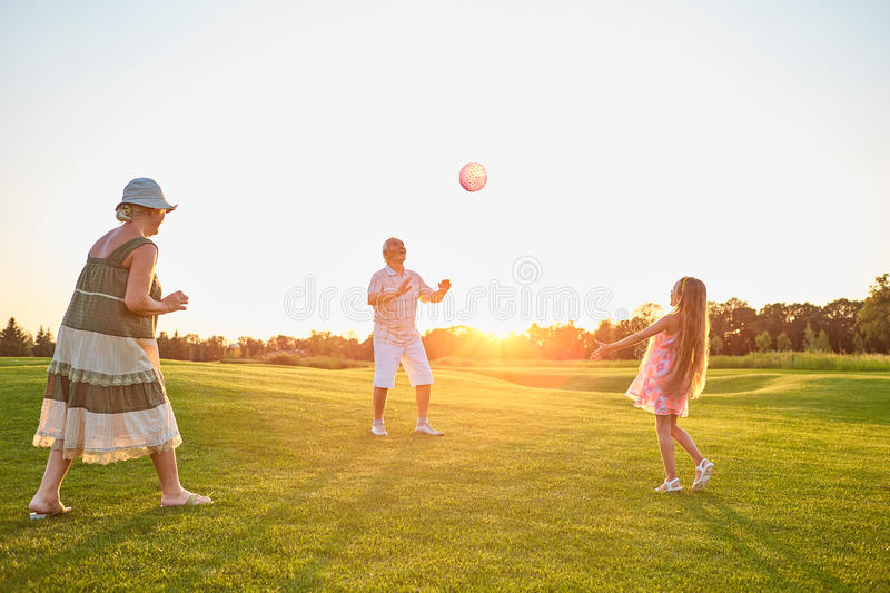 Seniors with child playing ball. stock photos