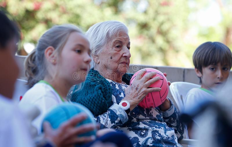 Seniors and childs during therapeutical activities on a nursing home in Mallorca. Seniors with childs practice some coordination games on the terrace of their stock photo