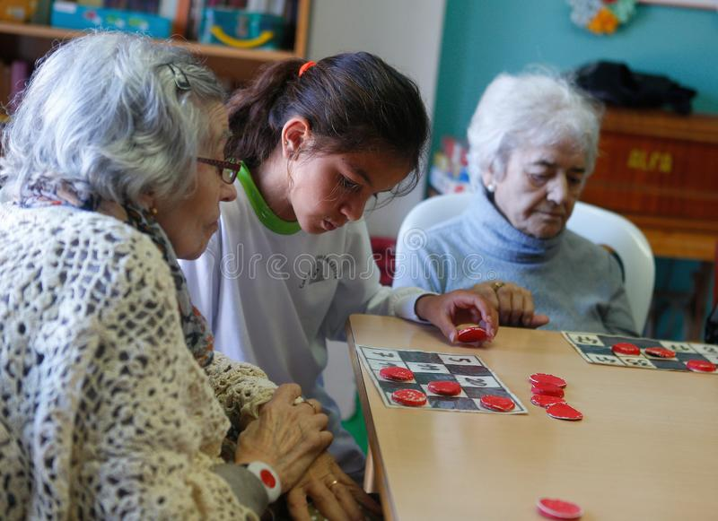 Seniors and childs during therapeutical activities on a nursing home in Mallorca detail. Seniors with childs practice some mind games on the terrace of their stock photography